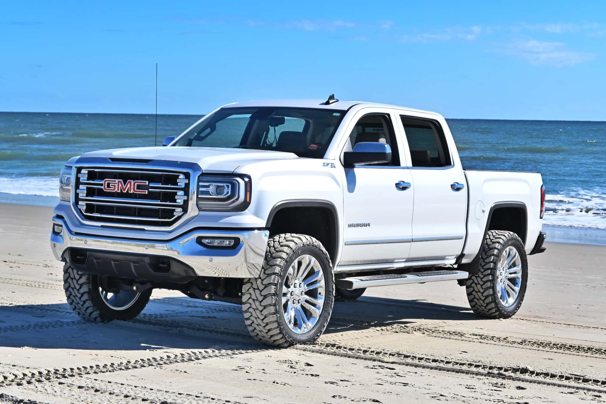A silver 2018 GMC Sierra 1500 running the Factory Reproductions Fr55 22x9 +24 wrapped in Toyo Tires Open Country M/t 35