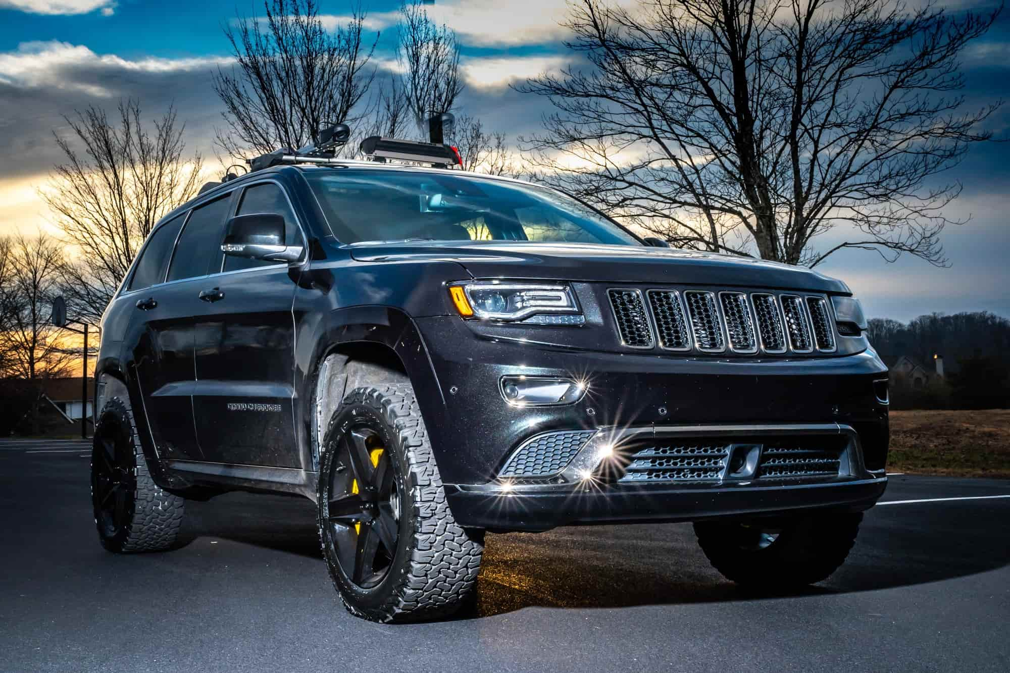 A grey 2015 Jeep Grand Cherokee running the Factory Reproductions Fr63 20x9 +34 wrapped in some tried and true BFGoodrich All Terrain Ta Ko2 275/55 and a AirLinks Leveling Kit