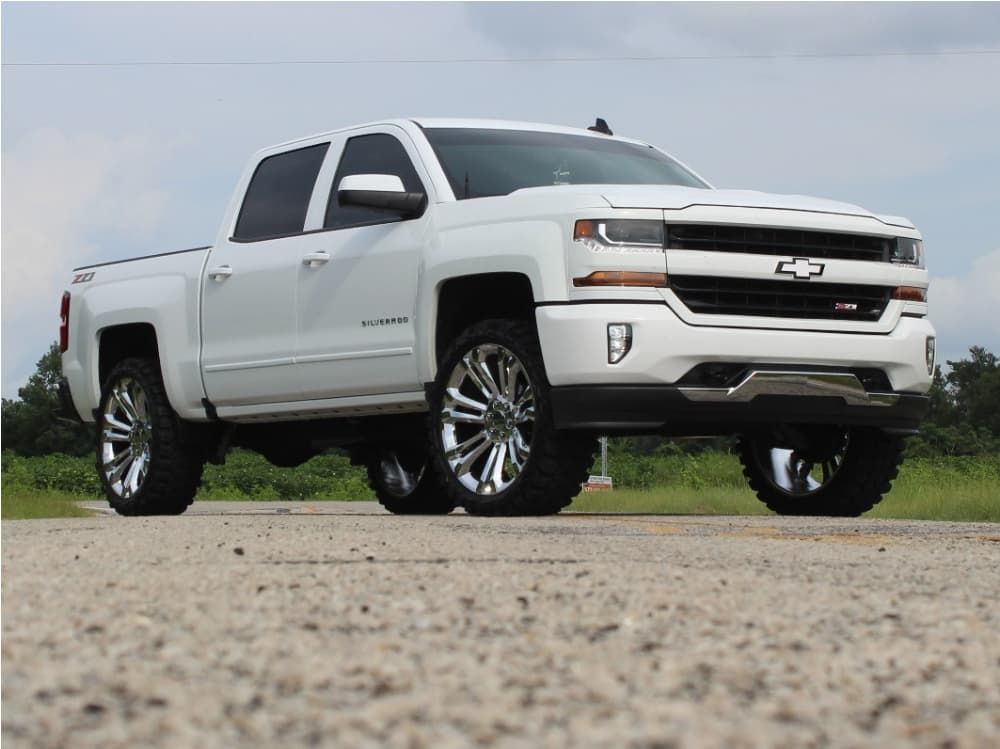 A white 2018 Chevrolet Silverado 1500 running Factory Reproductions Fr55 24x10 +31 wrapped in the Gladiator Xcomp Mt 35